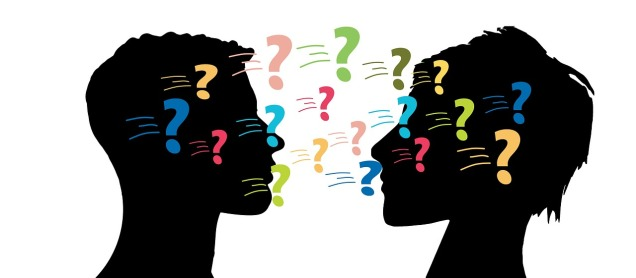 two silhouetted heads face each other, covered in colourful question marks